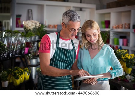 Smiling florists using digital tablet in florist shop
