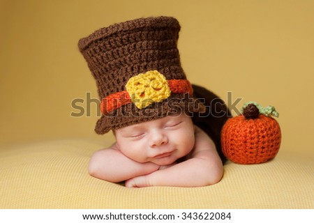 Smiling four week old newborn baby boy wearing a crocheted Pilgrim hat. He is sleeping on a gold blanket next to a crocheted pumpkin. - stock photo