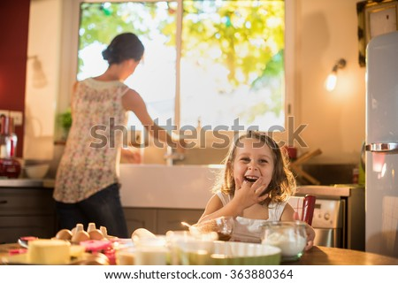 Smiling four years old blonde girl sitting at the kitchen table, licking chocolate on her fingers. Her mother is doing the dishes in the blurred background. They are cooking a tart.Shot with flare - stock photo