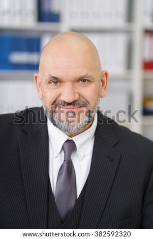 Smiling friendly balding middle-aged businessman with a goatee beard sitting at his desk in the office looking at the camera, close up frontal view - stock photo