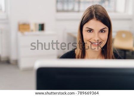 Smiling friendly businesswoman looking over the top of a large desktop monitor at the camera as she sits in the office