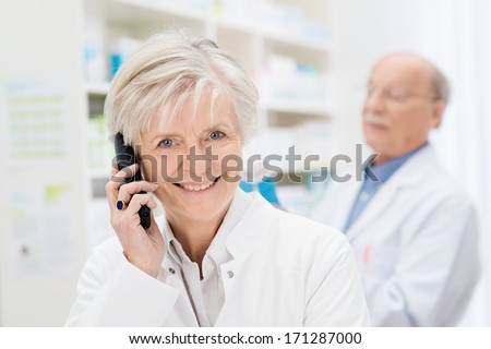 Smiling friendly female pharmacist chatting on the phone to a patient while her male colleague dispenses medicine in the background - stock photo