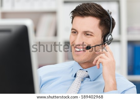 Smiling friendly handsome young male call centre operator or client services personnel beaming as he listens to a call and checks information on his computer monitor - stock photo