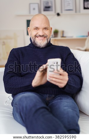 Smiling friendly man relaxing at home with his feet up on the sofa and a mobile phone in his hand, focus to his face - stock photo