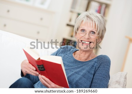 Smiling friendly senior woman sitting on a couch in her living room at home reading a book and looking up at the camera with a vivacious smile - stock photo