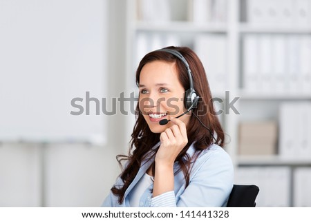 Smiling friendly woman wearing a headset sitting in an office, conceptual of customer support, receptionist or a call centre operator - stock photo