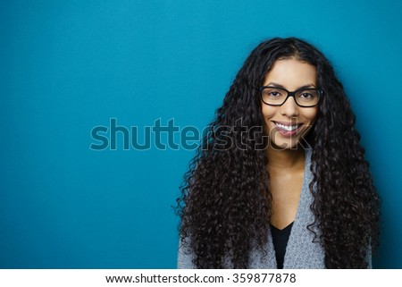 Smiling friendly young African American woman with lovely curly long black hair wearing glasses posing against blue background with copy space - stock photo