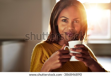 Smiling friendly young black woman drinking a cup of fresh coffee as she relaxes at home backlit by a bright high key sun flare - stock photo