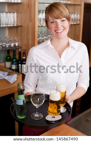 Smiling friendly young waitress serving drinks in a bar carrying a tray laden with beer and a bottle of mineral water - stock photo