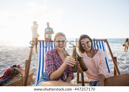 Smiling friends cheering with beer at the beach - stock photo