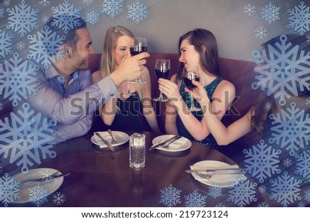 Smiling friends clinking wine glasses against snowflake frame - stock photo