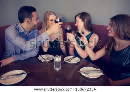 Smiling friends clinking wine glasses and chatting in a restaurant - stock photo