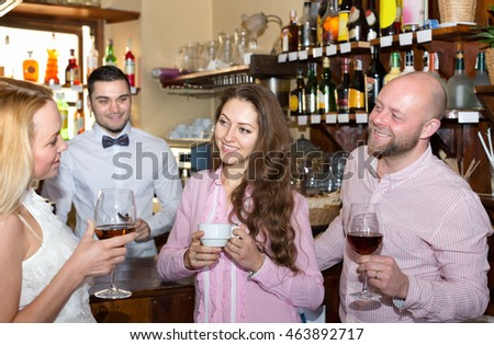 Smiling friends drinking and chatting with barman at bar counter