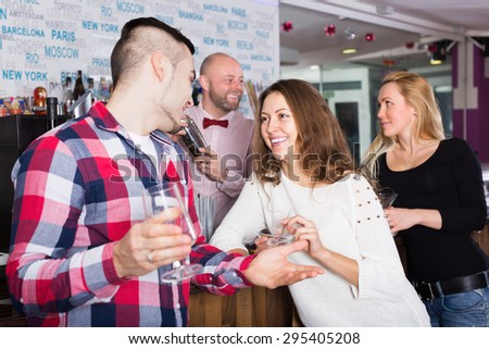Smiling friends drinking and chatting with positive barman at bar counter - stock photo