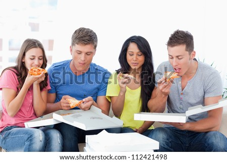 Smiling friends eat the slices of pizza in front of them