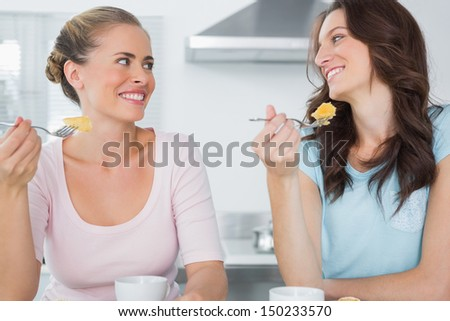 Smiling friends eating cake and having coffee in the kitchen - stock photo