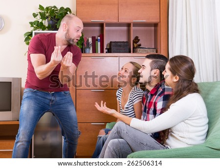 Smiling friends hanging out with beer and jokes at home