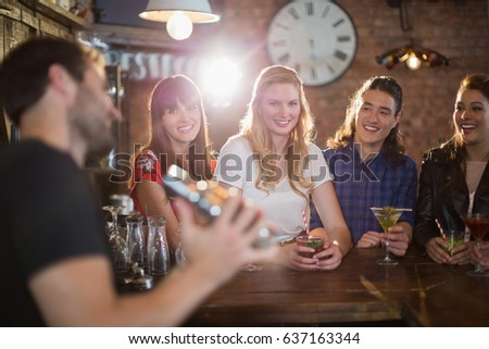 Smiling friends looking at bartender making drinks in pub