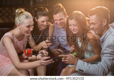 Smiling friends looking at mobile phone while having cocktail in bar
