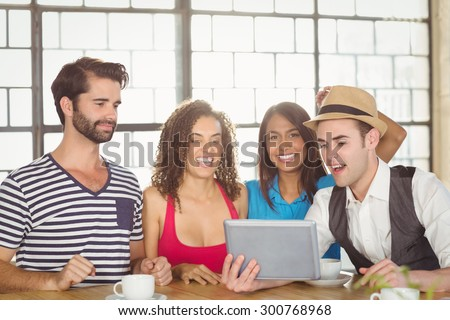 Smiling friends looking at tablet computer at coffee shop