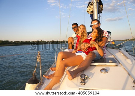 Smiling friends on yacht deck and greeting. Travel and vacation concept - stock photo