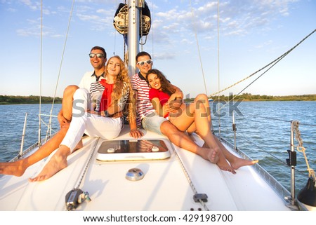 Smiling friends on yacht deck and greeting. Travel and vacation concept