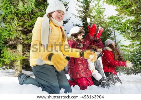 Smiling friends playing with snow in winter woods - stock photo