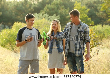 Smiling friends relaxing and clinking bottles in the forest outdoors - stock photo