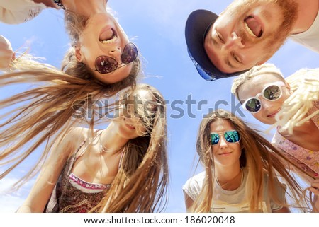 Smiling friends standing together in circle on background blue sky.  Reflection of the photographer - stock photo