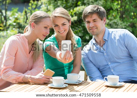 Smiling Friends Taking Selfie On Mobile Phone With Cup Of Tea On Table