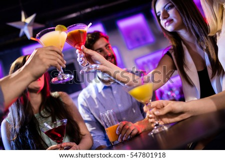 Smiling friends toasting cocktail at bar counter in bar