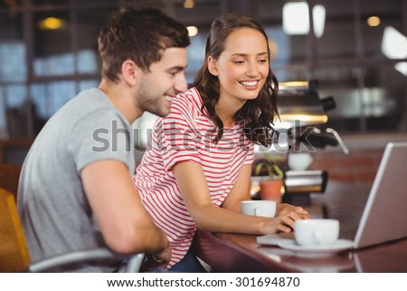 Smiling friends using laptop and having coffee together at coffee shop