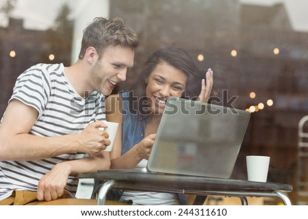 Smiling friends with a hot drink using laptop in cafe at the university - stock photo