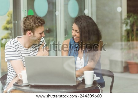 Smiling friends with chocolate cake using laptop in cafe at the university - stock photo