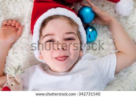 Smiling funny child in Santa red hat holding Christmas gift in hand, Christmas concept - stock photo