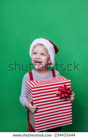 Smiling funny child in Santa red hat holding Christmas gift in hand. Christmas concept. Studio portrait over green background - stock photo