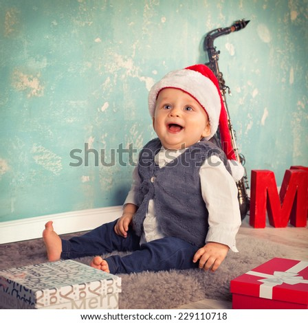 Smiling funny child in Santa red hat with Christmas gift. Christmas concept. - stock photo