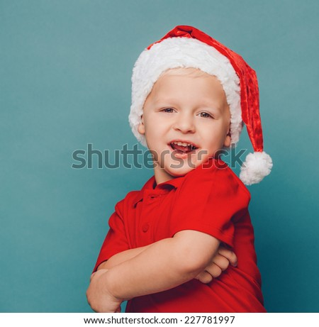 Smiling funny child (kid, boy) in Santa red hat.  Christmas concept. Shooting on blue background