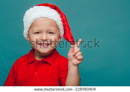 Smiling funny child (kid, girl) in Santa red hat. Christmas concept. - stock photo