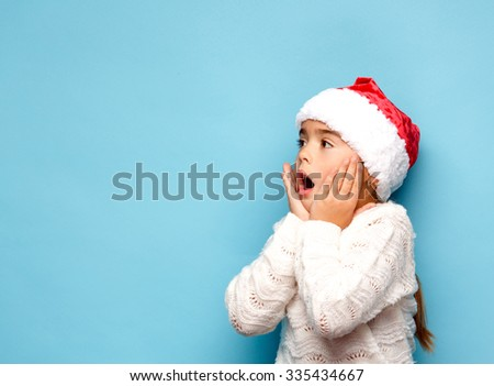 Smiling funny child (kid, girl) in Santa red hat.. Christmas concept. Shooting on blue background