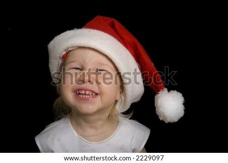 smiling funny little girl in christmas Santa red hat, isolated on black