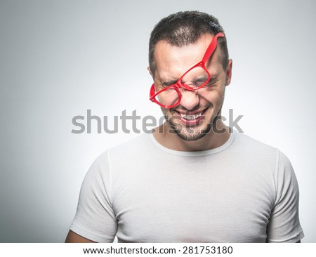 Smiling funny man wearing eyeglasses, isolated on bright gray background, studio shot. Laughing nerd