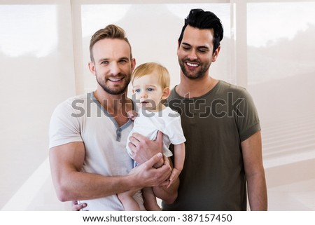 Smiling gay couple with child at home - stock photo