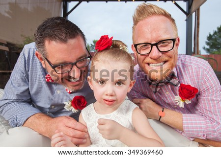 Smiling gay couple with daughter sitting outdoors - stock photo