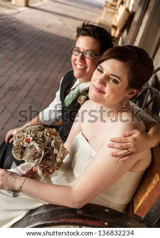 Smiling gay female couple sitting on rustic bench - stock photo