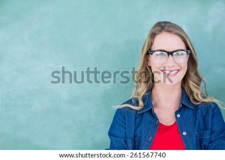 Smiling geeky teacher standing in front of blackboard in classroom - stock photo