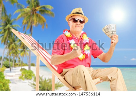 Smiling gentleman sitting on a beach chair and holding US dollars, on a beach near the sea - stock photo