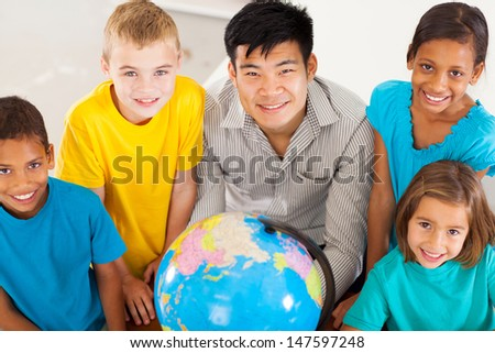 smiling geography teacher with group of adorable primary students - stock photo