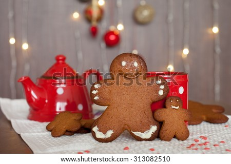 Smiling gingerbread man and a smaller one next to him standing in front of a mug. Teapot and more cookies on the background. Lights and christmas decoration in the background. Red and brown colors - stock photo