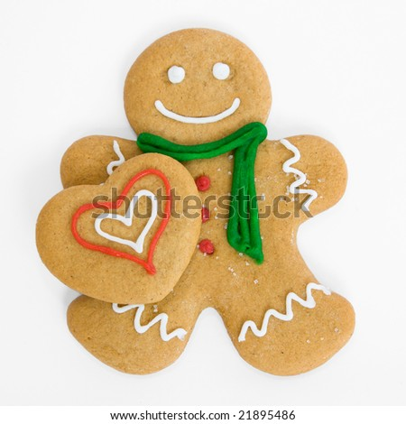 Smiling gingerbread man holds iced gingerbread heart